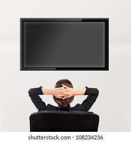 Woman watching tv. Photo from behind. Editable copyspace at the screen