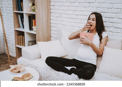 Woman Watching a TV. Woman is a Young Brunette Pregnant Girl. Girl Sitting on Couch. Woman is Eating a Lot of Popcorn. Person is Smiling. Different Food on Table. Person Located at Home.