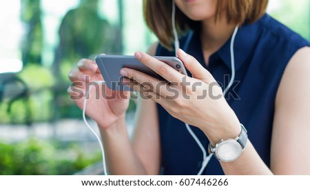 A woman is watching a video on her mobile phone  with headphones