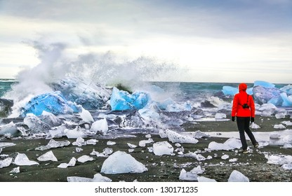 Woman watching waves crash against icebergs at Jokulsarlon glacial lagoon near Vatnajokull National Park, southeast Iceland
