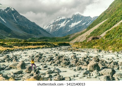 Woman at water stream on the Hooker trail tramping trek. Dramatic. Snow capped Mount Cook Mountain background. Grey cloudy moody. Green outdoors nature concept. Shot in Pukaki, New Zealand.