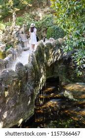 Woman at the waterfall Lake at Quinta da Regaleira, Sintra, Portugal