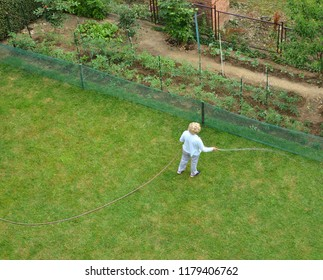 Woman watering a garden lawn shot from above - bird's-eye view