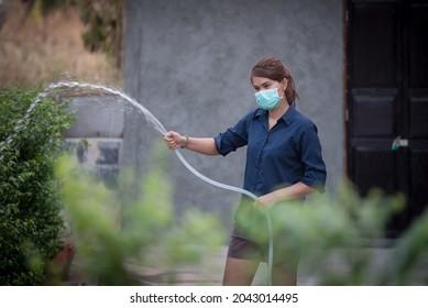 woman watering plants, woman watering plants during lockdown covid 19