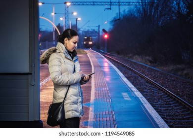 A woman is wating for a train and uses a smartphone at a railway station on the background of a railway and a catchy train at night, Glasgow, Scotland. Consent has been given for this photo.