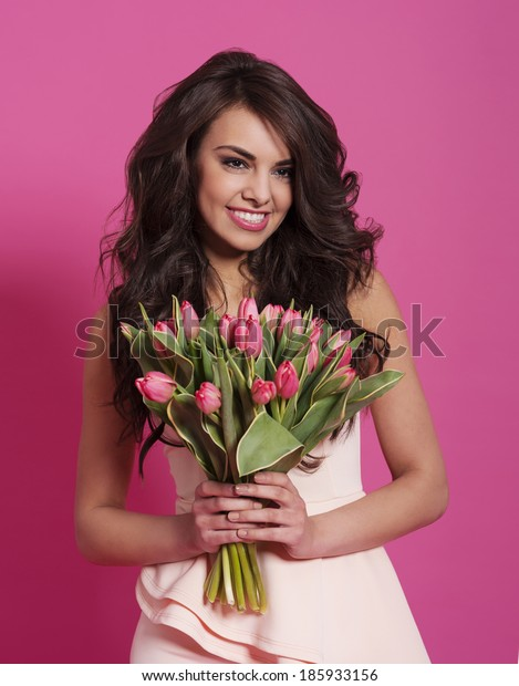 Woman in wavy hair holding spring bouquet
