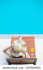 Woman wear big hat lay on wood bed beside swimming pool with blue water. There is glass of orange juice near her.