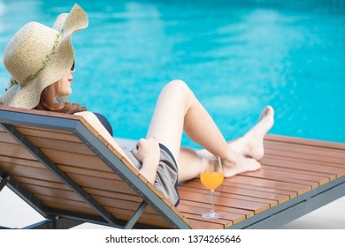 Woman wear big hat lay on wood bed beside swimming pool with blue water and looking to somewhere. There is glass of orange juice near her.