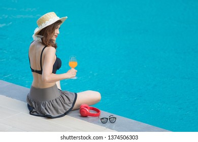 Woman wear big hat sitting  beside blue water swimming pool with red headphone and sunglasses, looking to somewhere. There is glass of orange juice in hand.