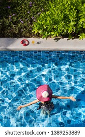 Woman wear big hat spread arms and walking in swimming pool going to glass of orange juice and red headphone.