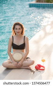 Woman wear bikini  sitting  beside blue water swimming pool with red headphone and sunglasses, looking to somewhere. There is glass of orange juice near her.