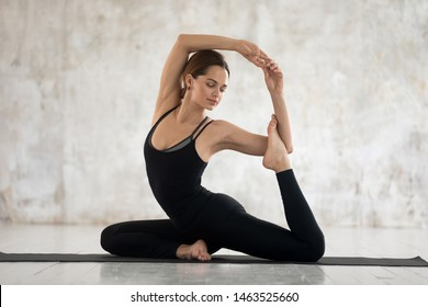 Woman wear black comfortable sportswear practising yoga on mat against beige grunge studio wall, young female performs Mermaid Pose Eka Pada Rajakapotasana asana, physical mental health care concept