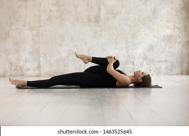 Woman wear black sport clothes lying on floor practising asana do Half Knees to Chest Pose near grunge wall beige textured background, help ease back pain, flexible body stretch for beginners concept