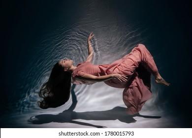 Frauen tragen Modekleid mit rosafarbenem Modemantel unter Wasser. Attraktives Young Lady Model mit Long Brunette Hair und tragen Luxus-Kleidung schwimmen in sauberem Wasser mit Projektor Light Horizontal Foto