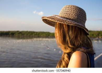 Woman wear hat looking to the sea and seagull crowd on sunset time. Young asian girl wearing hat looking away to the sea.