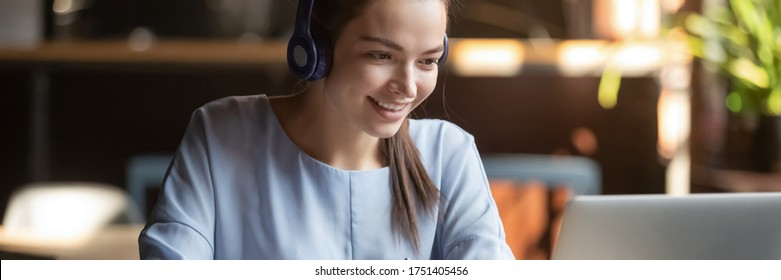 Woman wear headphones look at pc enjoy study online with tutor, listen audio lecture watch webinar prepare for exams, e-learn, self education concept. Horizontal photo banner for website header design - Shutterstock ID 1751405456