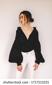 Woman wear long puff sleeve black fashion blouses, white jeans, silver necklace and low bun. Woman look sensual and sexy. Detail of evening elegant look. Renaissance Shirt, Avant Garde Clothing.