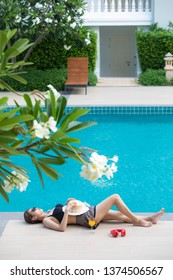 Woman wear sunglasses lay and sleep  beside blue water swimming pool with plumeria flower in foreground and apartment room in background.