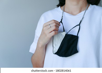 A woman wear white t-shirt hang cloth mask with strap anti lost or forgotten