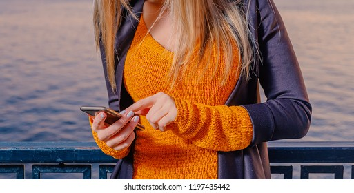 Woman weared in bright orange knitted jacket holding smartphone at night. She using application on mobile phone with touch screen interface.
