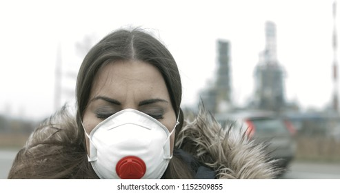 Woman wearing air pollution mask against smog, with urban industrial setting.