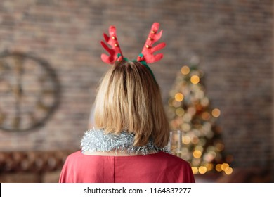 Woman wearing antler deer headband looking at decorated Christmas tree. Rear view. Christmas tree and wall clock on background. Christmas concept