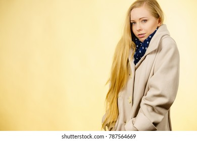 Woman wearing autumnal beige coat feeling cold. Fall overcoats, outfit and fashion concept. Studio shot on yellow background