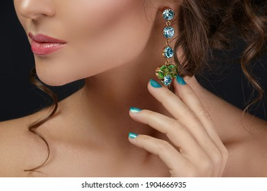 Woman wearing beautiful and expensive earrings with colorful gems