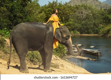 Woman wearing beautiful orange dress is riding the mighty elephant