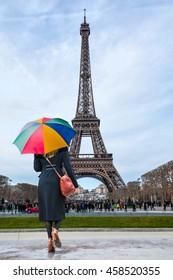 Woman wearing black dress, hand bag, belt and umbrella walking in Paris, France