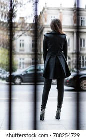 Woman wearing black elegant long coat and black high heel shoes in old town. Young beautiful business sexy woman walking, urban background. Back view of a fashion woman legs.