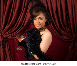 Woman wearing black feather boa, black feather fascinator, back lace choker and black corset, standing in front of red curtains and holding an orange drink in a martini glass.