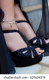 Woman wearing black glitter high heel wedge strap shoes with silk dress and ankle bracelet closeup