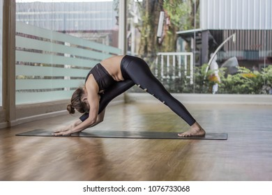 Woman wearing a black gym is playing yoga.