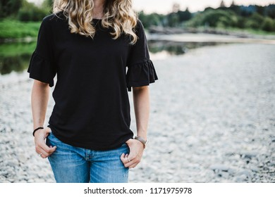Woman wearing black with hands hooked in pockets