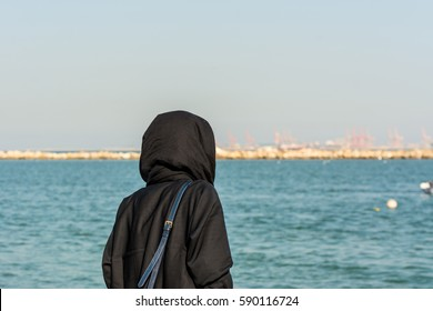A woman wearing black hijab looking at the sea at the corniche park in Dammam, Kingdom of Saudi Arabia