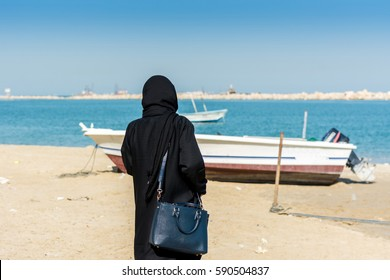 A woman wearing black hijab and a luxury bag looking at the sea at the corniche park in Dammam, Kingdom of Saudi Arabia