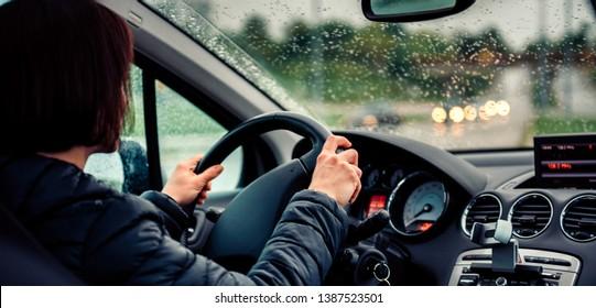 Woman wearing black jacket driving car on the motorway in the rain