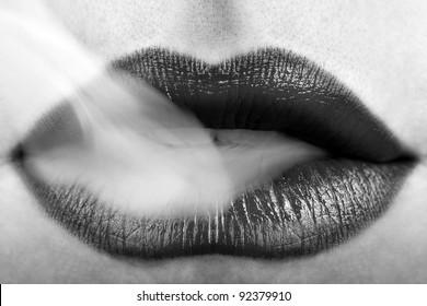 Woman Wearing Black Lipstick and Blowing Smoke