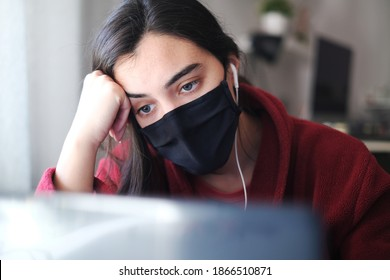A woman wearing a black mask trying to stay focused while working from home due to Covid-19, struggling with anxiety and depression. Mental illness awareness