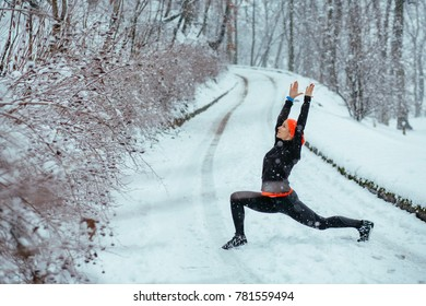 Woman wearing black and orange sportswear training exercising stretching outside during winter snowy day. Healthy lifestyle and cold weather concept.