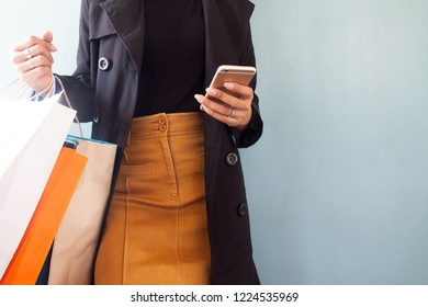 Woman wearing black overcoat using mobile phone and shopping bags on hand, Shopping concept