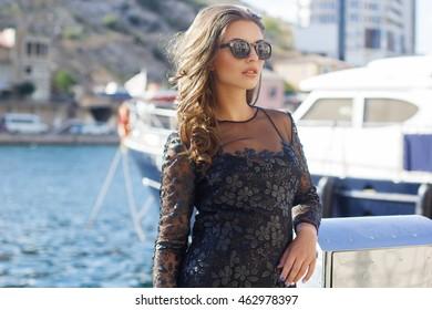 Woman is wearing black sunglasses near yacht