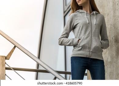 Woman wearing blank grey hoodie, in the city street background