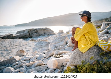 Woman wearing blue hat and yellow dress sitting on a beach and looking into horizon