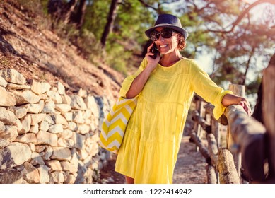 Woman wearing blue hat and yellow dress standing at a wooden fence by the sea and talking on phone