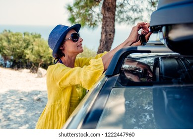 Woman wearing blue hat and yellow dress opening cargo box on roof rack at beach