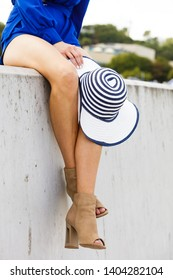 Woman wearing blue jumpsuit dress shorts perfect for summer holding elegant stylish sun hat.