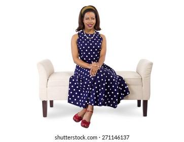 woman wearing a blue polka dot dress sitting on a vintage chaise lounge