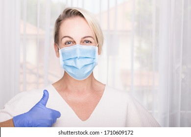 Woman wearing blue surgical mask and latex gloves giving thumbs up. Hospital environment. Healthcare concept.